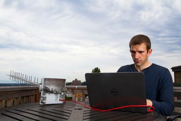 Ben Caudill sits at his laptop with a radio antenna
